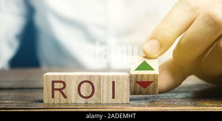 Wooden blocks with the word ROI and green arrow up. High level of business profitability. Return on investment, invested capital, rate. Success. Growt - Stock Photo