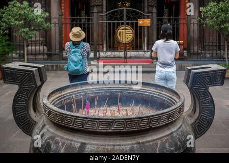 Chengdu, China -  July 2019 : Chinese woman and man praying, worshiping, burning incense sticks, giving alms and thanks at the Wenshu Chinese Buddhist - Stock Photo