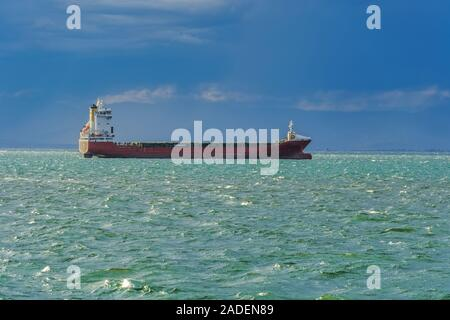 Sea transportation dry cargo vessel moored on sea with low waves. Freighter merchant bulk ship carrier at Thermaic Gulf outside port of Thessaloniki. - Stock Photo