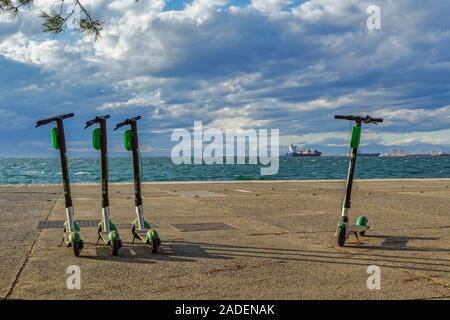 Parked Green & black ride sharing Lime-S electric scooter rentals without passenger at waterfront next to the sea in Thessaloniki, Greece. - Stock Photo