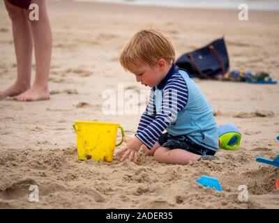 Batu ferringhi beach , Malaysia - November 2019 : Blonde baby boy playing on white sands beach bear hands and colorful toys near his parent - Stock Photo