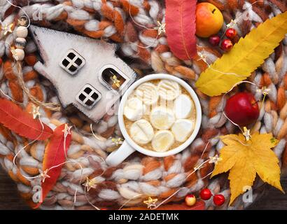 Autumn composition. Cup of cocoa with marshmallows, wooden hut, colorful leaves and scarf on table. - Stock Photo