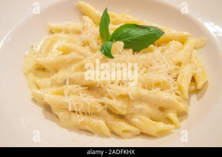 Pasta Penne four cheese with Basil, close-up, traditional Italian recipe, top view - Stock Photo