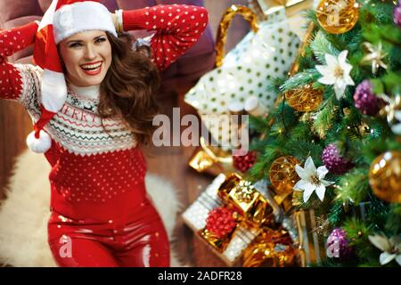 Upper view of relaxed stylish middle age woman with long brunette hair wearing red white Christmas sweater and elf santa hat sitting under decorated C