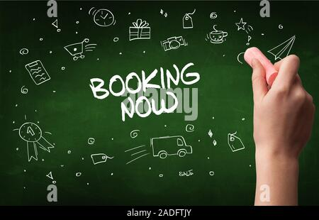 Hand drawing BOOKING NOW inscription with white chalk on blackboard, online shopping concept - Stock Photo
