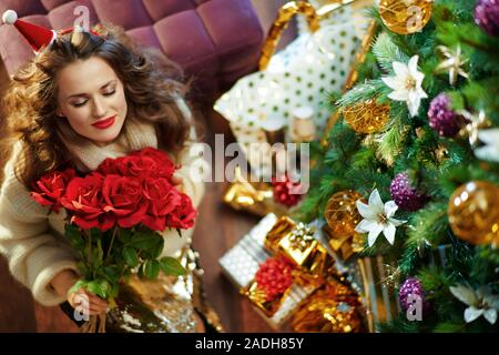 Upper view of smiling trendy middle age woman with long brunette hair in gold sequin skirt and white sweater under decorated Christmas tree near prese - Stock Photo