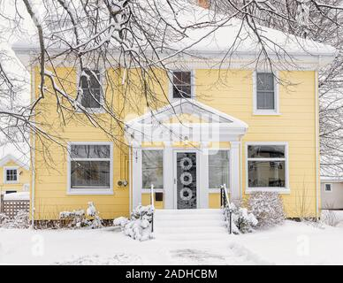 Traditional older family home covered in snow. - Stock Photo