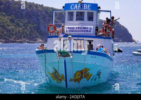 Tourists on a pleasure vessel at tiny Pantaleu island, San Telmo, Mallorca, Balearic islands, Spain - Stock Photo