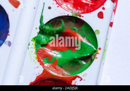 A stain of red paint in a can of green paint. A palette of paints. Modern art. Paint splash. Colorful curl.