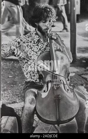 Fine black and white art photography from the 1970s of a street musician playing the string bass - Stock Photo