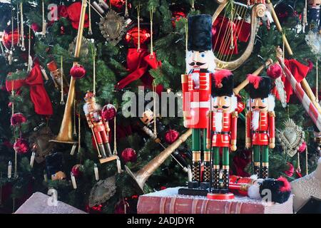 Soldier nutcracker wooden statue standing in front of decorated Christmas tree on an old book - Stock Photo