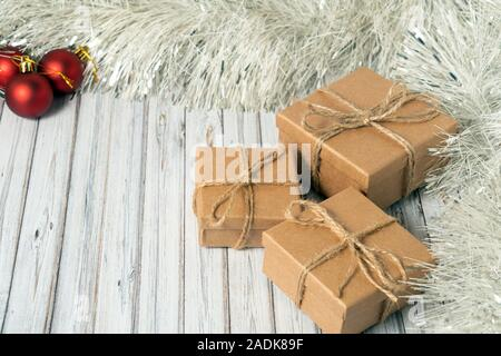 Three gift boxes on a wooden table decorated with a garland and red Christmas balls for the New Year or XMAS. Mail, courier or delivery service - Stock Photo