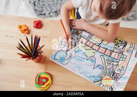 Conception of art. Cute little girl in art school draws her first paintings by pencils and markers