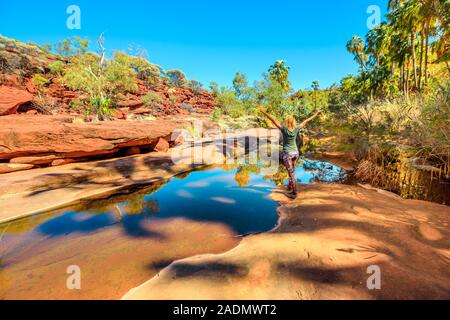 Carefree woman enjoying sandstone cliffs and red Cabbage Palm reflecting on waterhole in Palm Valley Oasis, Finke Gorge National Park. Tourism Outback - Stock Photo