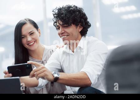Capture on the camera these awesome results. Young professionals. Cheerful coworkers in a modern office smiling when doing their job using smartphone - Stock Photo