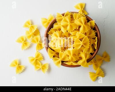 Pasta farfalle in wooden bowl on gray stone table. Top view, close up - Stock Photo