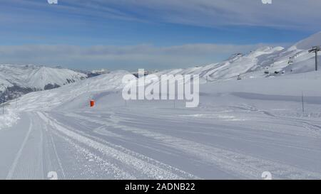 Alpine downhill ski slope with fresh snow, mountain peaks in the background, on a cold winter day - Stock Photo