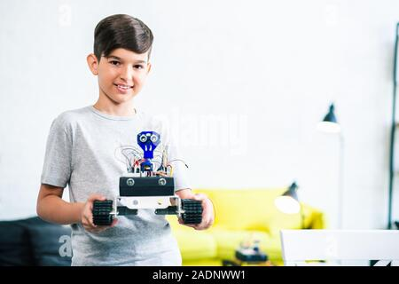 Pleasant little boy holding his robot at home - Stock Photo