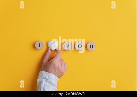 Male hand making an I love you sign spelled on wooden cut circles with marble heart shape in the middle. Over yellow background. - Stock Photo