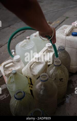 Caracas, Miranda, Venezuela. 29th Nov, 2019. Aura filling the water contaners with the water from her sister's house.Aura Graciela Sarmiento, age 56, and her husband Jose Alberto Abreu, age 62, have not had running water at their house in 4 years. Aura works in a store selling office furniture, and Jose is a mechanic. They live in the neighborhood of Altos de Lidice in Caracas Venezuela. Altos de Lidice is a historic Chavista neighborhood. However, Aura is pro-Opposition, and has never supported the Chavez regime even though she has lived in this pro-Chavez/Maduro barrio her whole life. S - Stock Photo