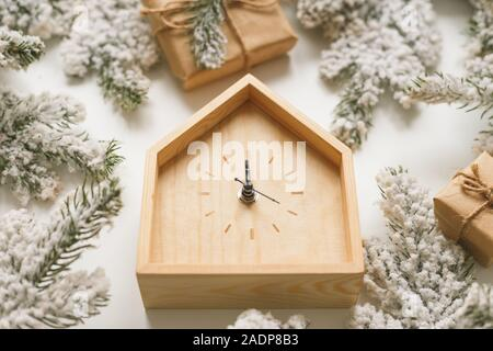 Christmas and New Year still life. Wooden clock shows five minutes to midnight. Fir branches and boxes around. View from above - Stock Photo
