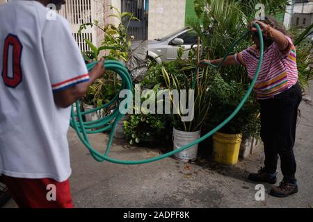 Caracas, Miranda, Venezuela. 29th Nov, 2019. Aura waters the plants with the water that is left in the hose after it is turned off. She does not waste any water.Aura Graciela Sarmiento, age 56, and her husband Jose Alberto Abreu, age 62, have not had running water at their house in 4 years. Aura works in a store selling office furniture, and Jose is a mechanic. They live in the neighborhood of Altos de Lidice in Caracas Venezuela. Altos de Lidice is a historic Chavista neighborhood. However, Aura is pro-Opposition, and has never supported the Chavez regime even though she has lived in thi - Stock Photo