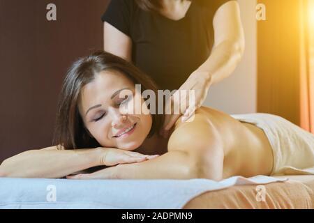 Professional back massage procedure, adult woman receiving treatment - Stock Photo