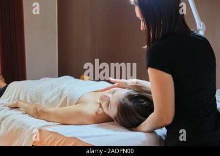Mature woman lying on massage table and receiving medical massage