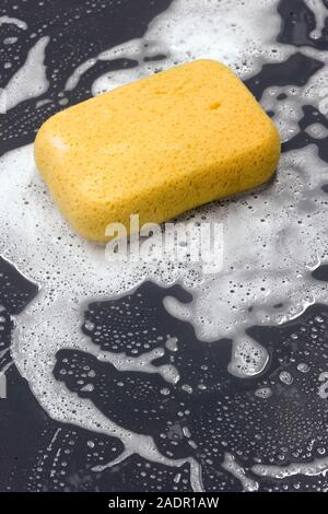 Still life of a  large sponge with water and soapsuds on a slate table - Stock Photo