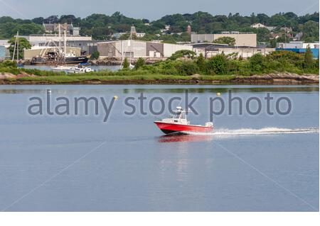 New Bedford, Massachusetts, USA - July 27, 2019: Men in powerboat cutting across New Bedford harbor - Stock Photo