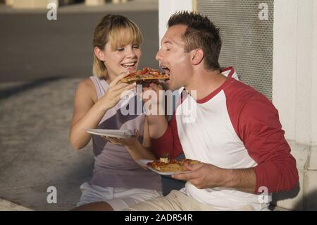 Junges Paar isst eine Pizzaschnitte - Young couple eating pizza outdoors - Stock Photo
