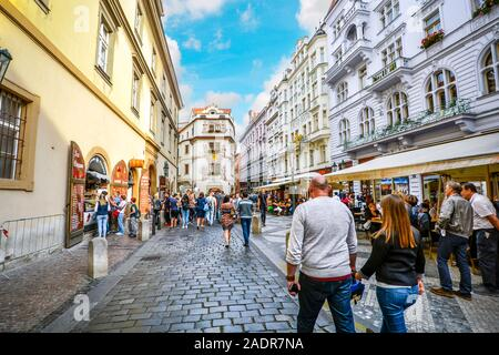 Tourists enjoy a sunny morning shopping and visiting cafes at a busy shopping street in the old town section of Prague, Czech Republic - Stock Photo