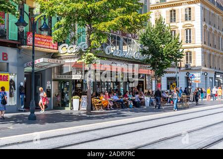 French locals and tourists enjoy an afternoon meal at a sidewalk cafe in Nice, France. - Stock Photo