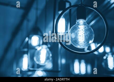 Vintage tungsten filament multiple lamps toned in color of the year 2020 classic blue. - Stock Photo