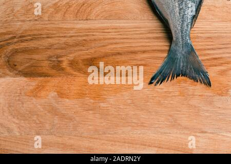 Copy space photo of wooden table with fish tail on the top - Stock Photo
