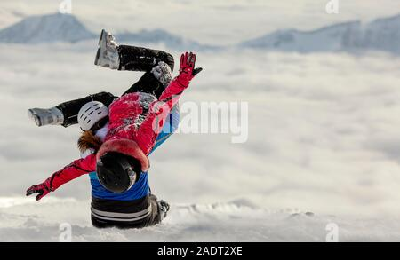Skiing family enjoying winter vacation. Young couple in love sitting on fresh snow in beautiful sunny cold day in mountains. Man liftting up his girl. - Stock Photo