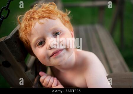 Portrait of a Toddler boy with messy face sitting on a swing outdoors