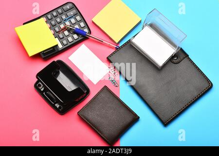 Calculator, hole punch, card holder, notebook, note paper, pen and clips. Business and work concept. Office tools isolated on pink and blue background, top view. Leather wallet and stationery. - Stock Photo