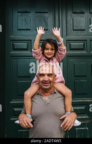 Grandfather carrying his granddaughter on his shoulders, very happy a - Stock Photo