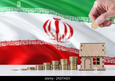 Man holding coins putting in wooden house moneybox, Iran flag waving in the background. Saving money for mortgage. - Stock Photo