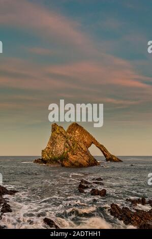 BOW FIDDLE ROCK PORTKNOCKIE MORAY SCOTLAND WINTER SUNSET WITH PINK CLOUDS AND FOAM ON THE ROCKS - Stock Photo