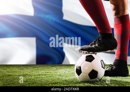 Close up legs of Finland football team player in red socks, shoes on soccer ball at the free kick or penalty spot playing on grass. - Stock Photo