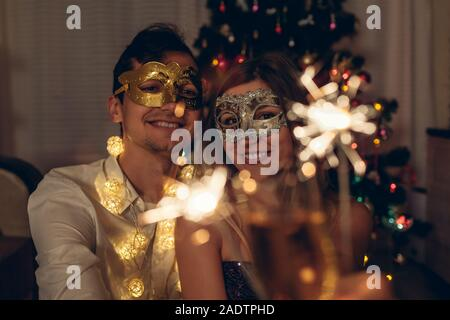 Christmas and New year party concept. Couple in love burning sparklers by illuminated Christmas tree with champagne. - Stock Photo
