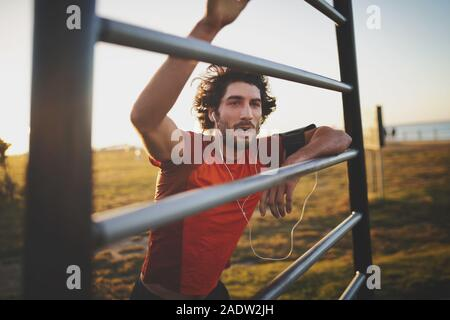 Young athletic man taking a break from training standing with hands on vertical bars at outdoor gym park in the morning