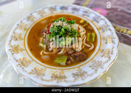 Traditional Mouthwatering Central Asian Uyghur Lagman Soup Dish with Vegetables on a Colorful Plate - Stock Photo