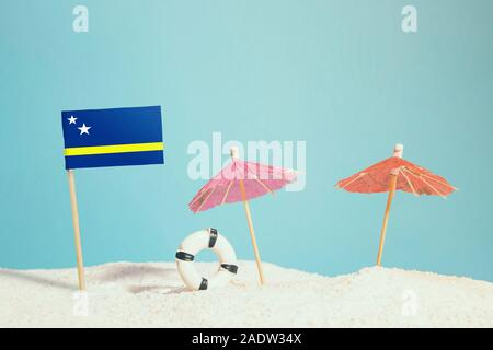 Miniature flag of Curacao on beach with colorful umbrellas and life preserver. Travel concept, summer theme. - Stock Photo