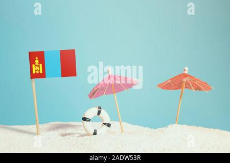 Miniature flag of Mongolia on beach with colorful umbrellas and life preserver. Travel concept, summer theme. - Stock Photo