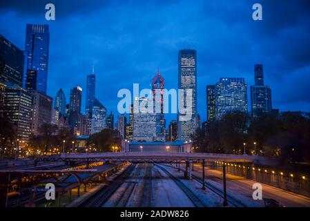 City skyline of illuminated skyscrapers in downtown Chicago Loop area and railway lines and people waiting for train, Chicago, Illinois, USA