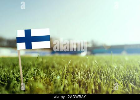 Miniature stick Finland flag on green grass, close up sunny field. Stadium background, copy space for text. - Stock Photo
