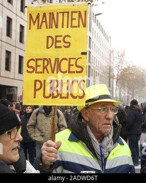 "December 5, 2019, Lyon, France: Workers, students, and pensioners march in Lyon, France to protest the Macron government's proposals to reform the French pension system..This man's sign translates as ""Maintain public services.?..Photo by James Colburn (Credit Image: © James Colburn/ZUMA Wire) - Stock Photo"